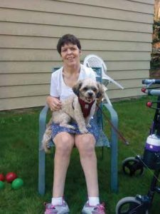 A disabled woman sitting in a chair with her small dog sitting on her lap