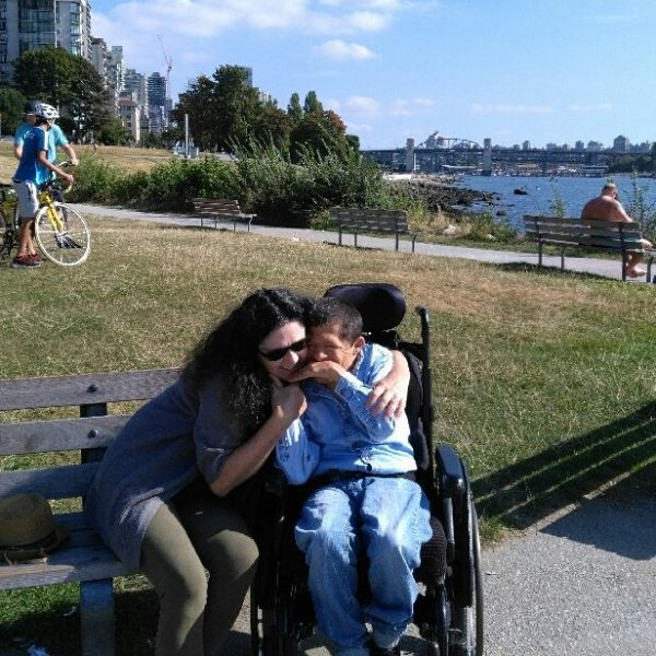 Man in wheelchair sitting on Vancouver beach