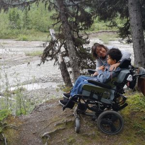 Young man in wheelchair with his mother sitting beside a river